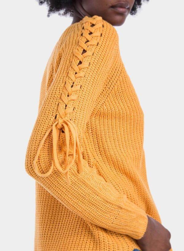 Pormenor da manga de camisola decote em V manga entrançada em amarelo para mulher da Tiffosi