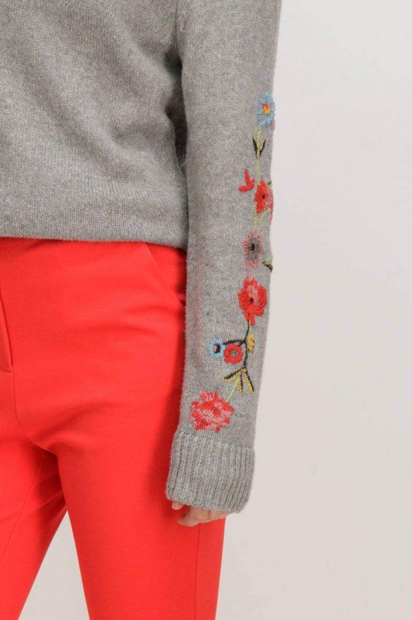 Pormenor de camisola cinzenta com bordados e decote redondo de mulher da Garcia Jeans